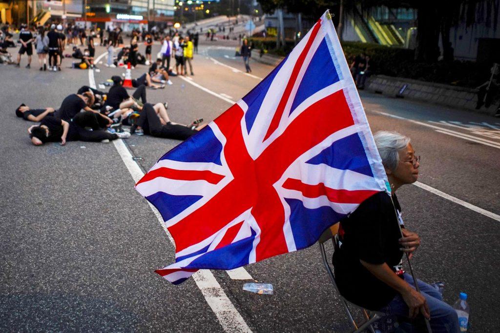 Una donna mostra la bandiera britannica a Hong Kong