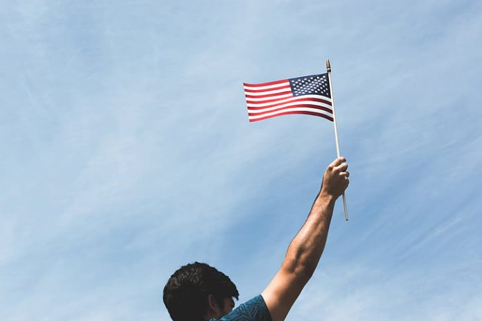 man holding US flag during daytime