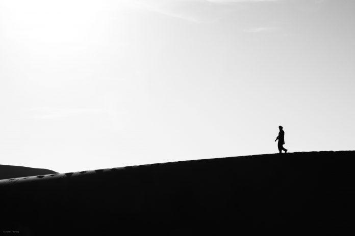 Fotografia di un uomo sulle dune del Sahara. Sicurezza alimentare migrazioni